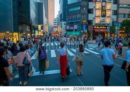TOKYO, JAPAN JUNE 28 - 2017: Unidentified people crossing the street using the crosswalk at Ikebukuro district of Tokyo metropolis, Japan. Tokyo Metropolis is both the capital and most populous city of Japan.