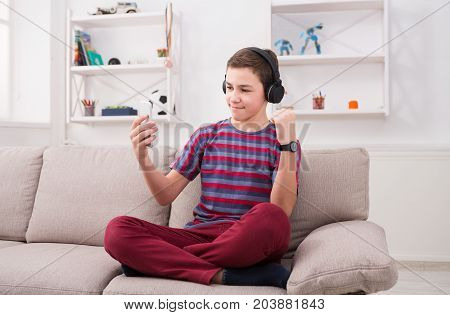 Teenage boy enjoying music in headphones at home. Making selfie and sharing with friends in social media, relax time
