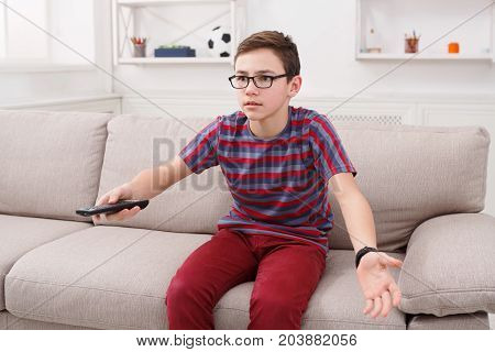 Surprised teenager boy watching television, using remote control to switch channels. Youngster curious at what he sees on TV screen. Sitting on couch in living room at home