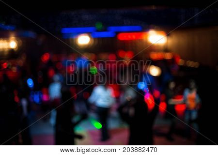 People dancing in night club blurred background. Beautiful blurred lights on dance floor people in spotlight rest at night in club