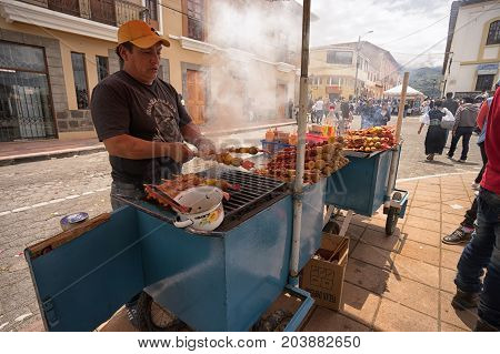 April 14 2017 Cotacachi Ecuador: street vendor preparing food on the wood fired barbecue during Easter procession