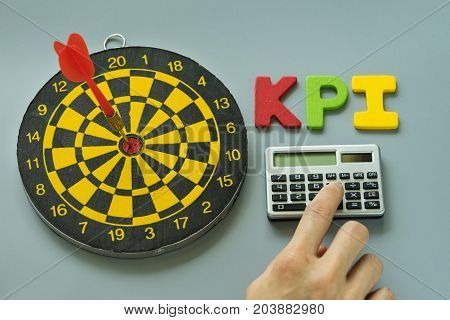 finger on calculator and colorful alphabet KPI with dartboard as Goals or Target concept.