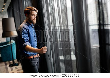 Handsome man looking at cityscape through skyscraper window