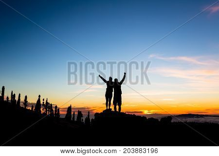 Teamwork couple climbing and reaching mountain peak. Silhouette of celebrating climbers team over mountains sunset. Man and woman hikers looking at inspirational landscape on Tenerife Canary Islands.