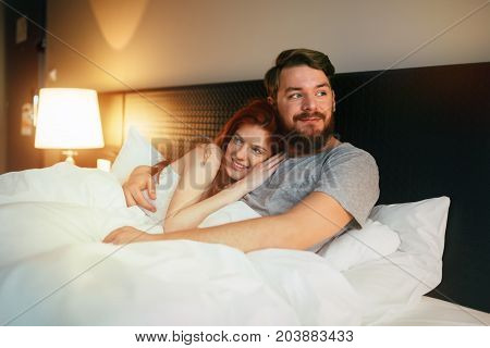 Sensual cute young couple in bed cuddling