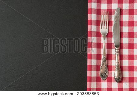 Silverware with red checkered towel and empty tag on blackc slate background. Top view. Menu card for restaurants.