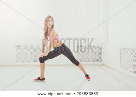 Fitness woman warmup stretching training at gym. Young slim girl makes aerobics exercise. Healthy lifestyle, weightloss, gymnastics concept