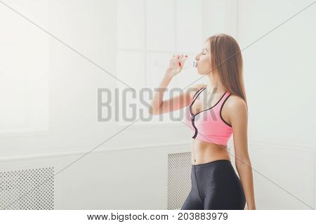 Beautiful young sport woman drinking water. Confident fitness girl holding plastic bottle, thirsty after training, healthy lifestyle concept