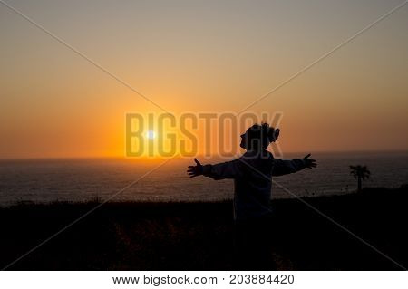 happy woman with arms outstretched at sunset on the beach with a silhouette background