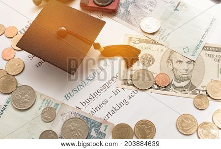 Graduation cap on book Business News Concept of graduate education in university requires a lot foreign currency Dollars bring success in study famous institution Concept of abroad international