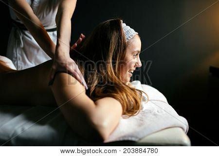 Beautiful woman enjoying massage treatment given by therapist
