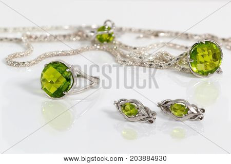 Close-up beauty silver earrings ring and pendant with peridot on background chain and ring on white acrylic desk.