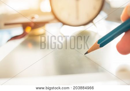 Alarm clock with Graduation cap and optical form of standardized exams or test on touch screen tablet with hand holding blue pencil for examination Education conceptselective focusvintage