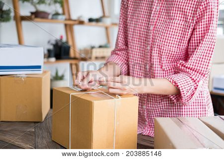 young start up small business owner packing cardboard box at workplace. freelance woman entrepreneur SME seller prepare parcel box of product for deliver to customer. Online selling internet marketing e-commerce shipping concept