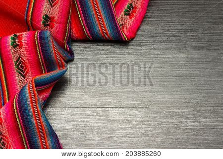 Multicolor pattern tablecloth on wooden table for background. Fabric texture. Wooden texture.Template for designers