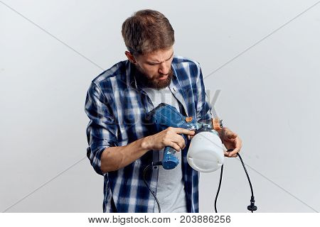 man in plaid shirt holding a construction tool.