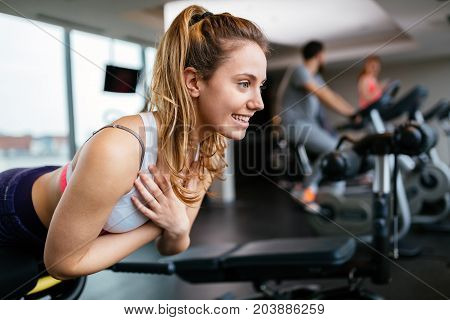 Beautiful woman working out in gym strengthening her back muscles