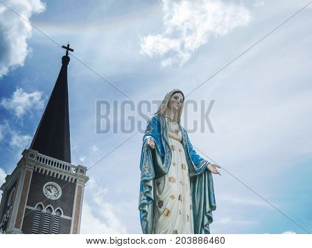 The Blessed Virgin Mary Statue blue sky background. and behind the Virgin Mary there are temples and crosses. On the sky there Sun halo
