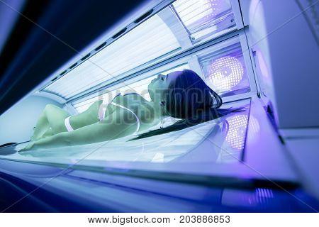 Beautiful sexy brunette woman sunbathing in solarium