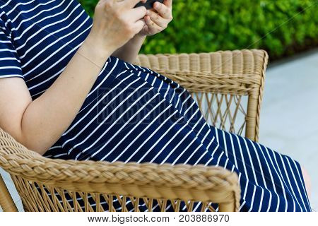 Pregnant Woman Play Smartphone While Sitting