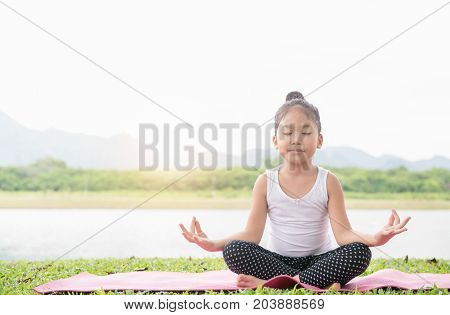 Happy Cute Girl Practices Yoga And Meditates In The Lotus Position
