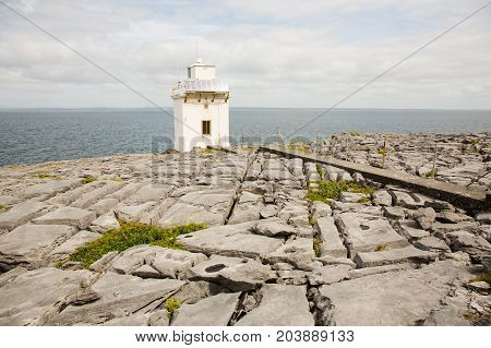 Irish coastline, sea and horizon, broken rock ground with light house