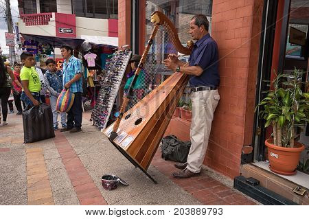 April 29 2017 Otavalo Ecuador: man playing the harp on the street in the Saturday market