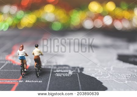 Miniature People Travelers Riding Bicycle On World Map