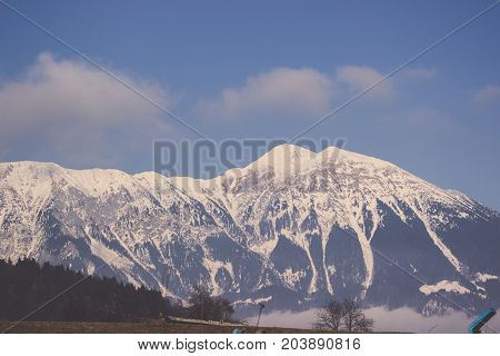 Landscape of winter sierra covered in snow under clear sky and clouds, View of white mountain range with small trees line and bright blue sky in Bled at Slovenia