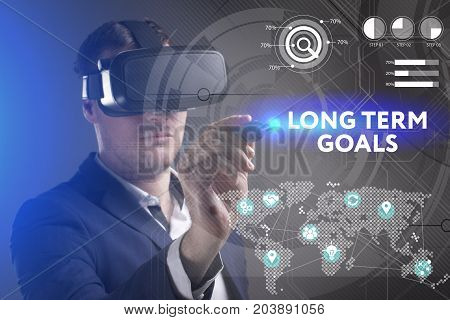 Business Technology Internet and network concept. Young businessman working in virtual reality glasses sees the inscription: Long term goals