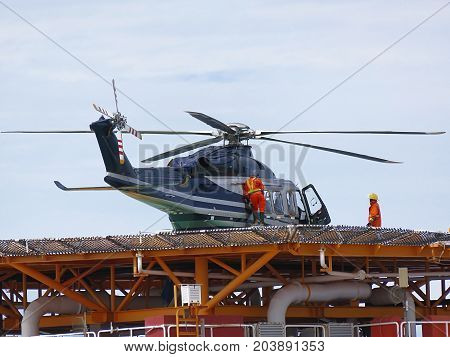 Helicopter or chopper land at oil and gas platform area for get and sent passenger from onshore hangar to offshore platform. Ground staff put in jet-A1 fuels in helicopter.