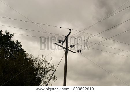 telegraph pole with telephone lines overcast clouds