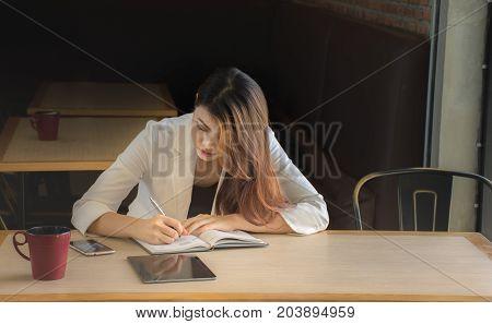 businesswoman  write strategic planning on notebook./Businesswoman makes a note in notebook.
