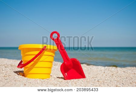 Yellow childrens bucket with red toy toy plastic red scapula on the left against the blue sea and blue sky yellow sand beach sea shore seashells summer vacation sunny summer day, bright sun, baby toys