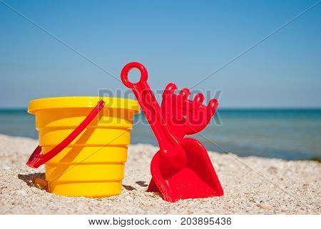 Yellow childrens bucket with red handle, plastic red scapula and rake left on a blue sea background and blue sky yellow sand beach sea shore seashells summer vacation sunny summer day, bright sun