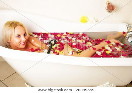 Young blond woman with big smile relaxing in rose petal Victorian bath