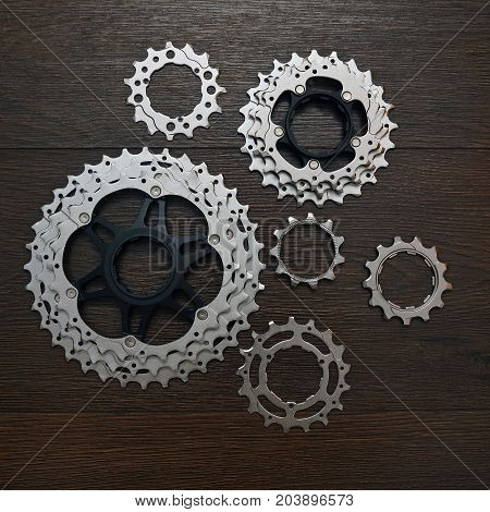 a few declutched bicycle gears on wood