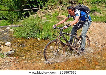 man crossing a creek on mountain bike
