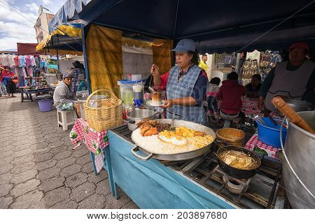 April 29 2017 Otavalo Ecuador: indigenous quechua women are preparing food on the street in the Saturday market