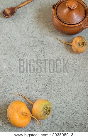 Fresh raw yellow turnip brown clay pot and wooden spoon on a gray background. Preparation of steamed turnips.