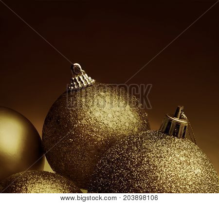 Close up view of golden color christmas balls against a bronze color background