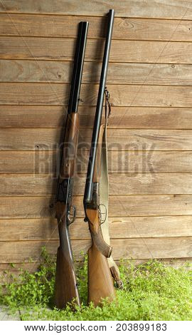 Two different (side-by-side & over/under) hunting double-barreled shotguns stand in the grass leaning against the plank wall