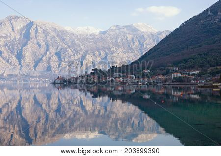 Mediterranean village of Stoliv with mountains and reflection in the water. Kotor Bay of Adriatic Sea Montenegro