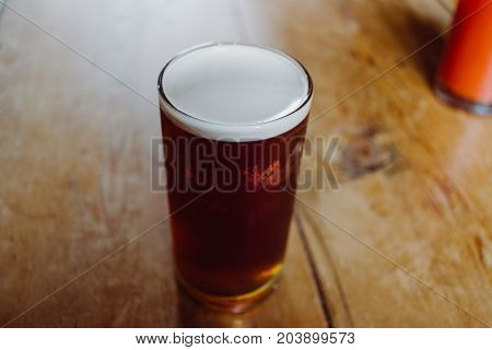 An English Ale Bitter Beer Pint On A Wooden Table In A Pub In Uk
