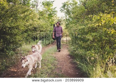 Handsome bearded man with guitar bag and husky dog walking in the woods at summer times