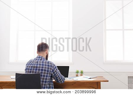 Successful male programmer background. Handsome manager in casual view from back with copy space on window. Relaxed man at work
