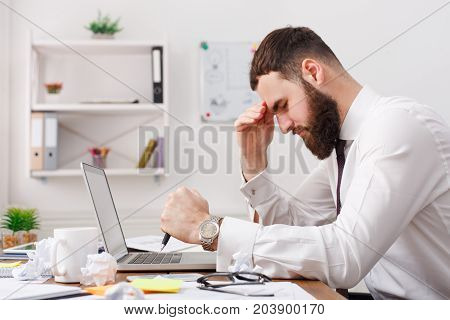 Thoughtful stressed frustrated man working for too long on computer, chooses solution, thinking about hard problem