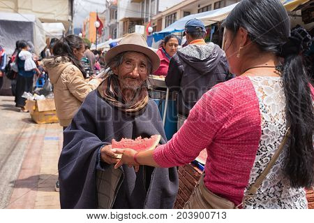 May 6 2017 Otavalo Ecuador: a woman hands over a slice of watermelon to a poor indigenous man