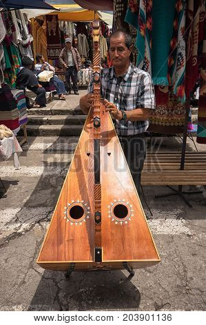 May 6 2017 Otavalo Ecuador: indigenous quechua man playing the harp in the Saturday market