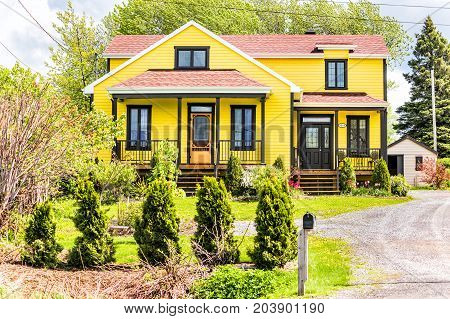 Ile D'Orleans Canada - June 1 2017: Yellow painted rural rustic house with road mailbox in summer landscape French countryside during summer
